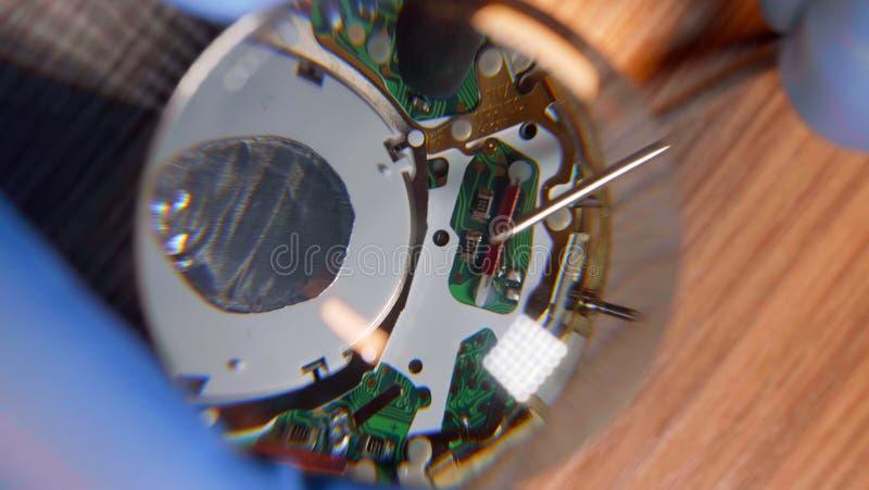 Horloger dans les gants fonctionnant la montre reparing de cru avec l'aide de la loupe photo stock
