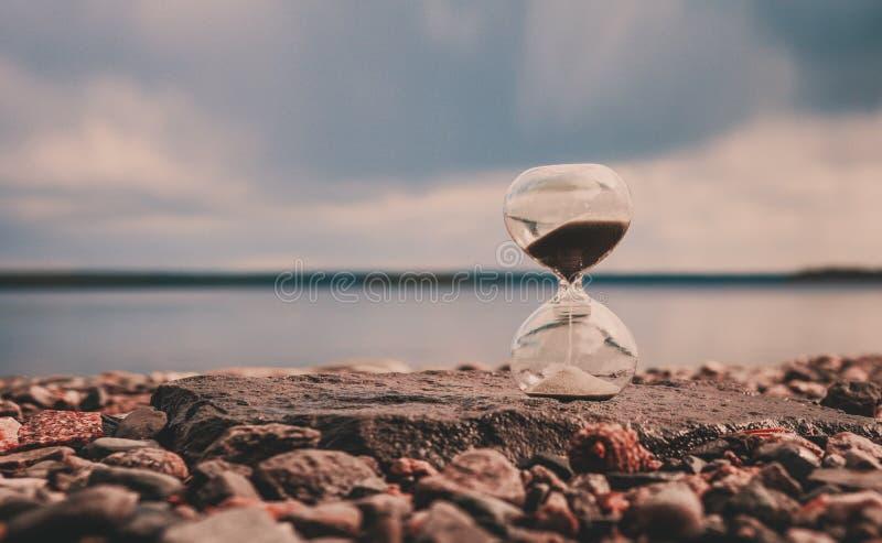 Hormigón en piedras cerca del lago, foto atmosférica de arena en caída en forma de reloj de vidrio, concepto de tiempo fotografía de archivo