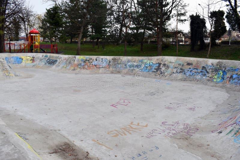 hormigón vacío que anda en monopatín patinador del monopatín del diseño del skatepark del parque del patín con la pintada imagenes de archivo