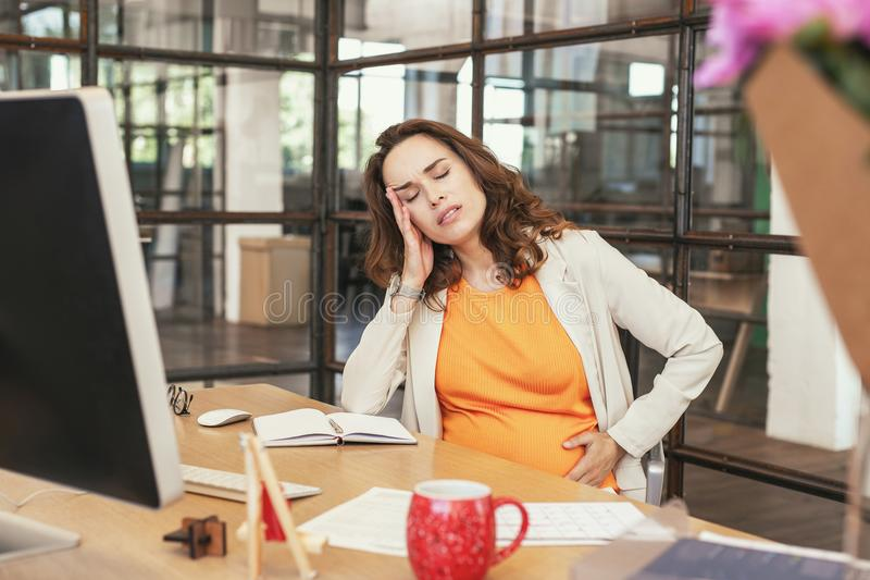Tired pregnant CEO feeling dizzy stock photo