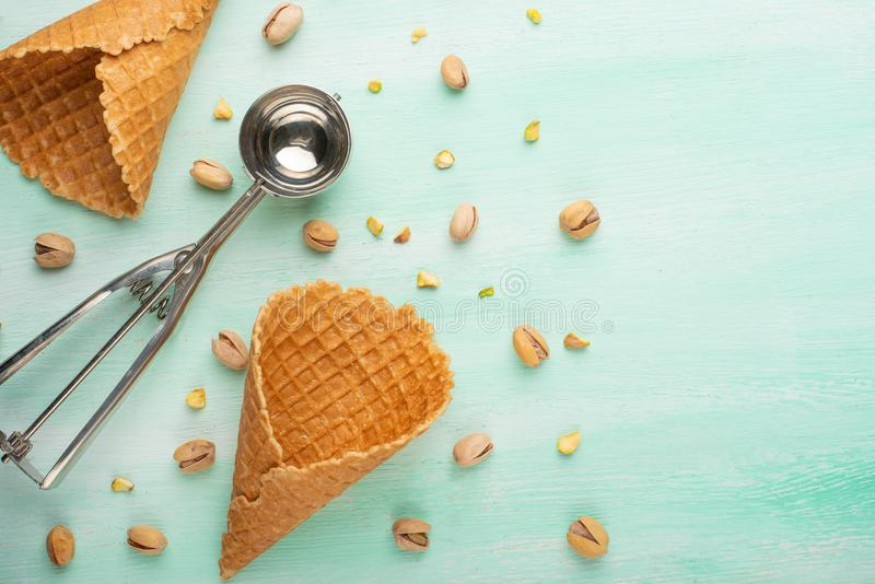 Horn with ice cream on a mint background with a spoon for ice cream and pistachio nuts. Summer mood.  stock images