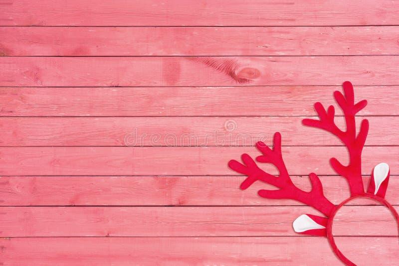 Horn på kronhjort av en hjorthuvudbindel på rosa träbakgrund Leksakrenhorn på rosa trätextur arkivfoton