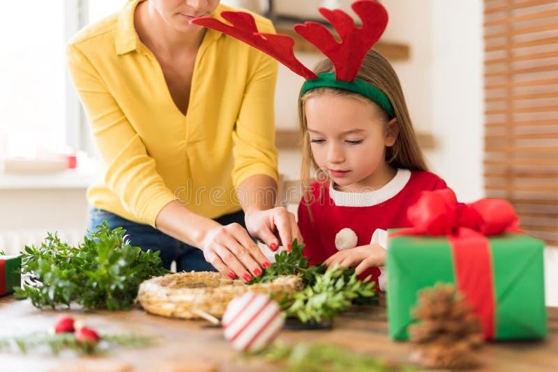 Horn på kronhjort för ren för gullig förskolebarnflicka bärande och hennes moder som gör julkransen i vardagsrum Lycklig fader oc royaltyfri bild