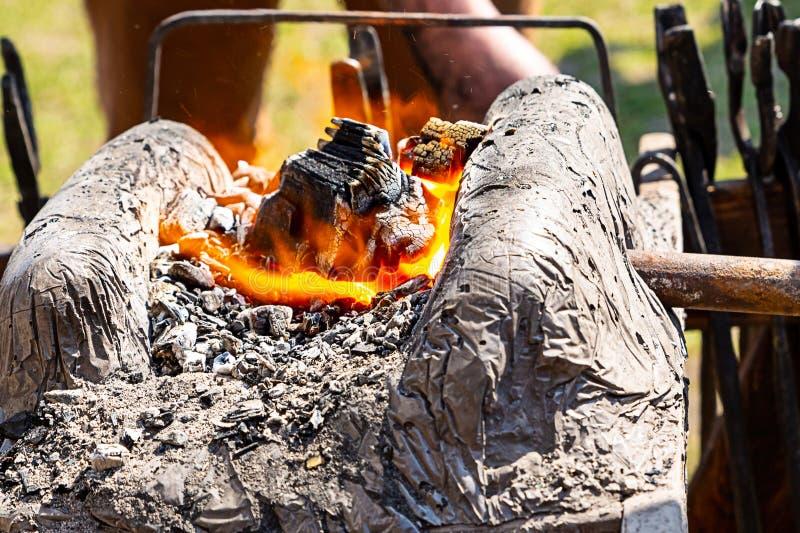 Horn- stenlera som utgjuter brandaskagrunden, smälter metall som gör vapensvärd som förfalskar produkter den traditionella vägen arkivbilder