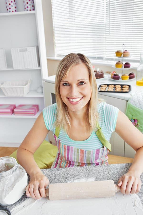 Hornada alegre de la mujer en la cocina imagen de archivo