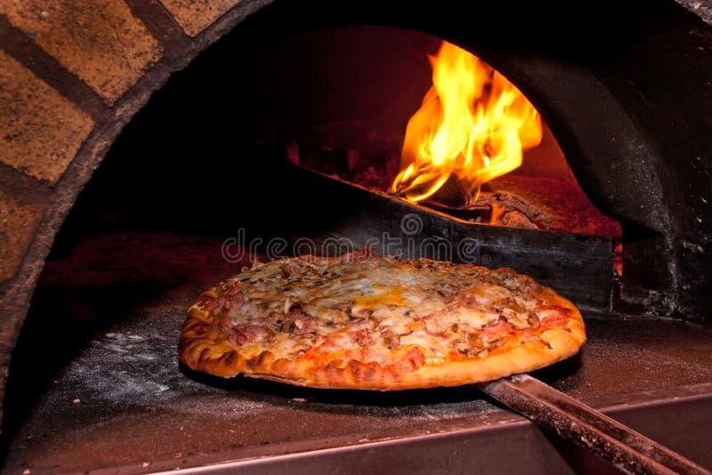 Hornada de la pizza en el horno imagen de archivo libre de regalías