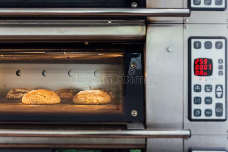 Hornada del pan hecho en casa en horno eléctrico Horno de la producción en la panadería Pan de la hornada Fabricación de pan fotos de archivo