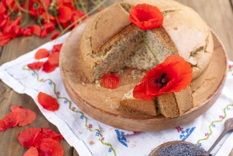 Hornada hecha en casa Torta del desayuno con la amapola y la fruta cítrica Estilo rural y ramo de flores rojas de la amapola Fond fotografía de archivo libre de regalías