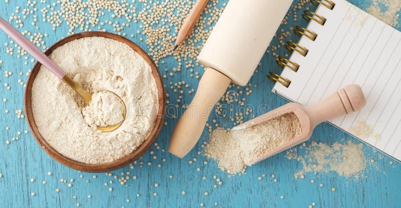 Hornada libre del gluten con la harina de la quinoa en cuenco de madera foto de archivo