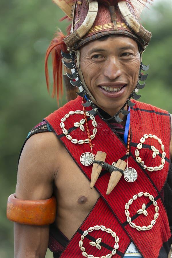 Hornbill-Festival Nagaland, Indien: Am 1. Dezember 2013: Junger Naga-Stammes- Mann, der ein offenes Lächeln am Hornbill-Festival  lizenzfreie stockfotografie