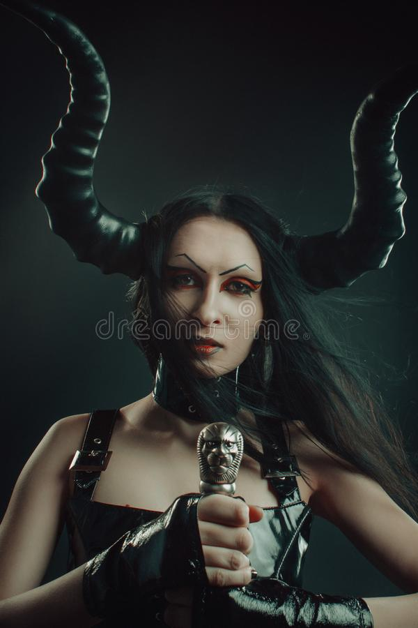 Horned demonisk flicka med svärdet royaltyfri bild