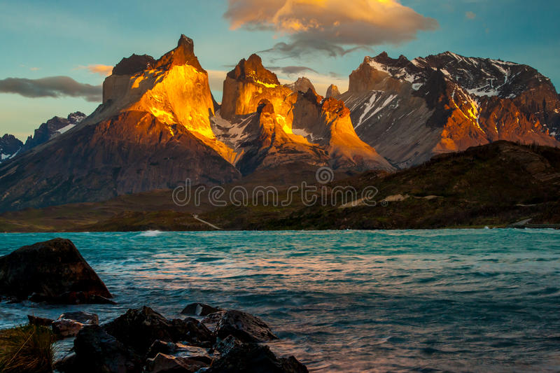 Hornes of Torres del Paine. Vertical Composition of Sunrise Over Torres del Paine With Shore of Lake Pehoe In Foreground royalty free stock image
