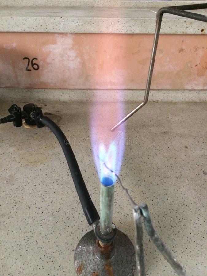 Hornilla de Bunsen con el alambre de cobre que parte la llama azul por la mitad foto de archivo