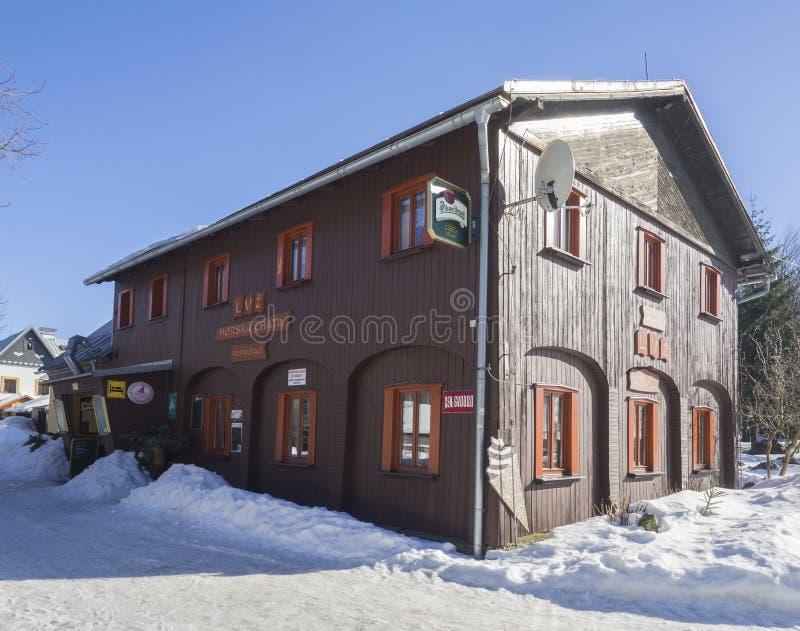 Hornisvetla, Tsjechische Republiek, 16 Februari, 2019: Houten bergplattelandshuisje Luz met restaurant, vorst en sneeuw in zonnig stock foto's