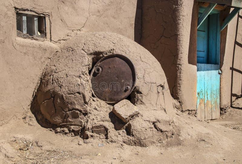 Horno - horno al aire libre del adobe del fango en comunidad al sudoeste del pueblo de los E.E.U.U. con el viejo top del barril d imagen de archivo