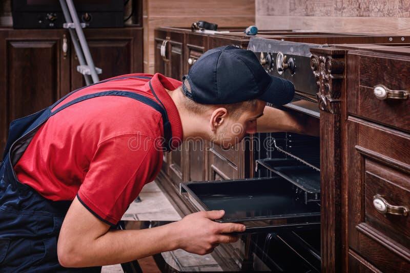 Horno de junta del trabajador profesional Instalación de los muebles de la cocina imagenes de archivo