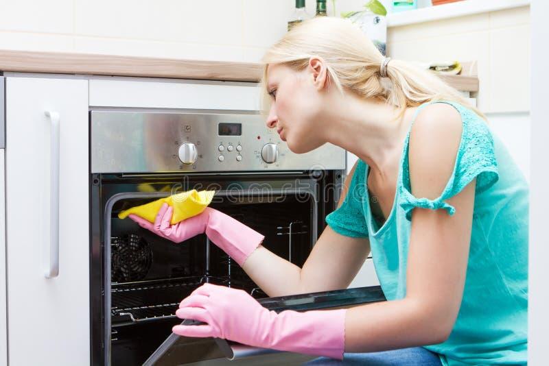 Horno de la limpieza de la mujer joven en la cocina fotografía de archivo