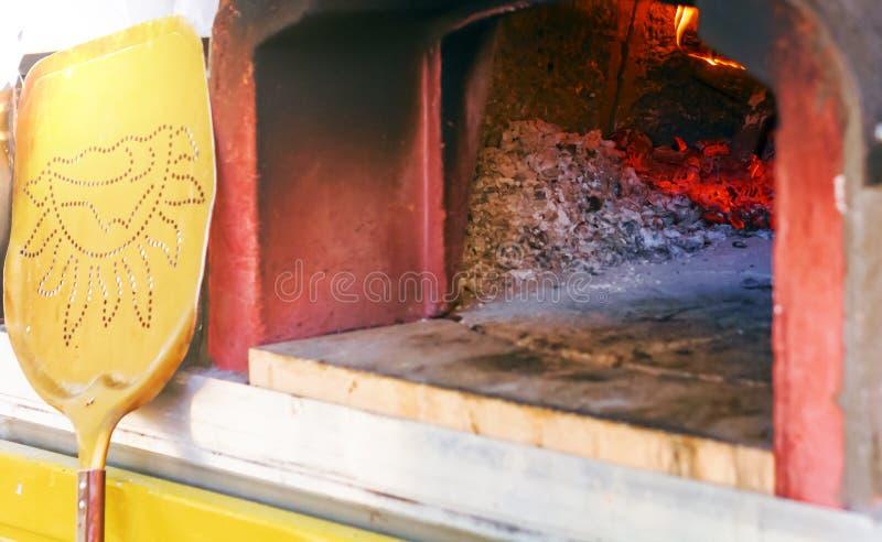 Horno de madera para la pizza que cuece con las cenizas, las ascuas ardientes y el fuego fotos de archivo libres de regalías