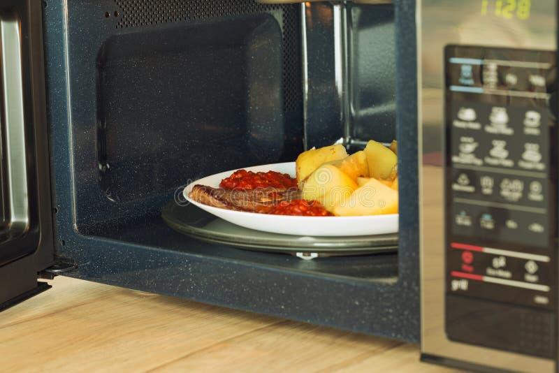 Horno de microondas con una comida heated foto de archivo