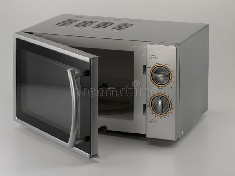 Horno de microondas en fondo gris imágenes de archivo libres de regalías