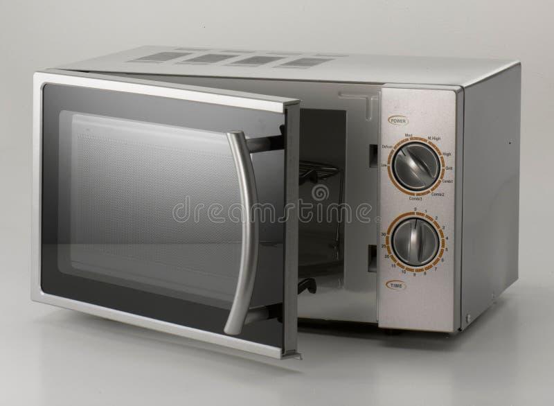 Horno de microondas en fondo gris foto de archivo