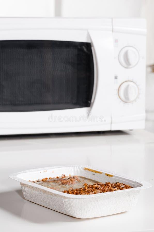 Horno microondas con el alimento congelado foto de archivo