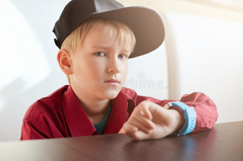 A horoizontal portrait of serious male child wearing trendy cap and red shirt having a smart watch on his wrist sitting at wooden royalty free stock photography