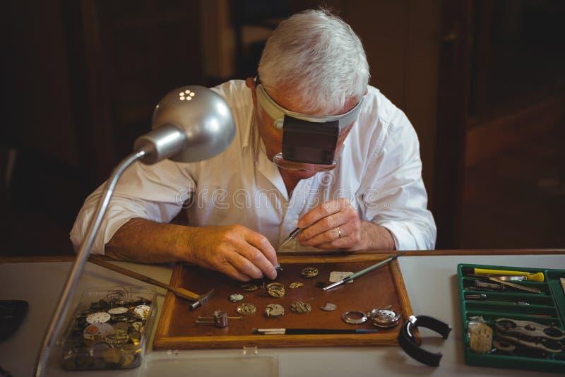 Horologist, der eine Uhr repariert stockfotografie