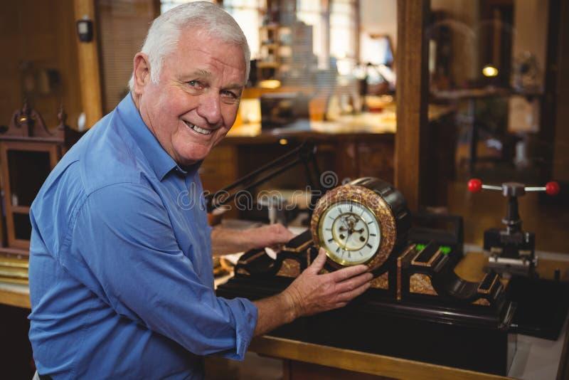Horologist sprawdza zegar w warsztacie obraz stock