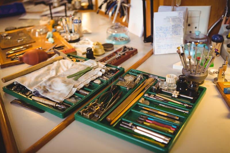 Horologistwerkstatt mit der Uhr, die Werkzeuge, Ausrüstungen und Maschinerie repariert stockbild