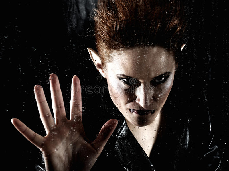 Horrible vampire woman behind rainy window stock photo