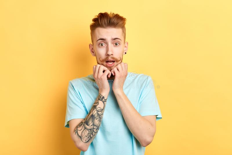 Horrified emotional young man keeps palms under chin, looking at camera. Horrified emotional young man being astonished with big sales prices,looks with eyes royalty free stock photos