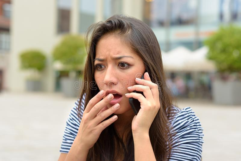 Horrified upset young woman talking on a mobile royalty free stock photos