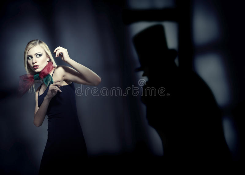 Horror. Blond afraid lady in the dark interior with deep shadows. Artistic colors and grain added royalty free stock photo
