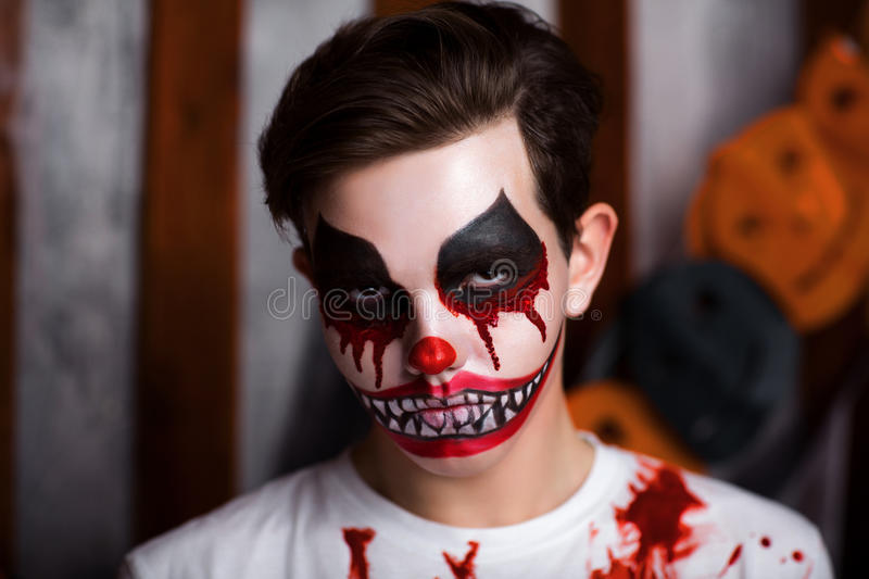 Horror clown makeup. Young guy with creative body painting horror clown. Boy is a carnival character with colorful makeup blood on face and shoulders. Big mouth royalty free stock images