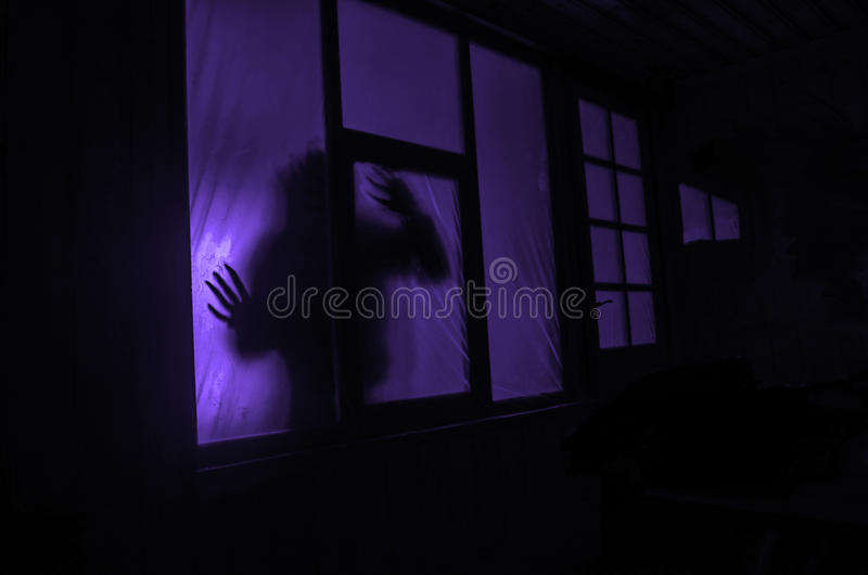 Horror concept. The silhouette of a human with sprayed arms in front of a window. at night. stock photos