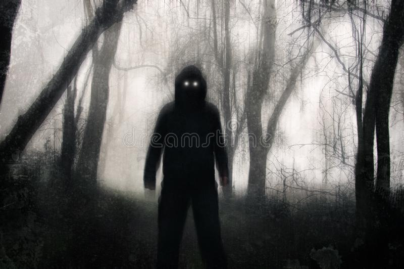 A horror concept. A silhouetted hooded figure, standing in a winter forest, with glowing scary eyes. With a grunge, texture,. Blurred edit stock photography