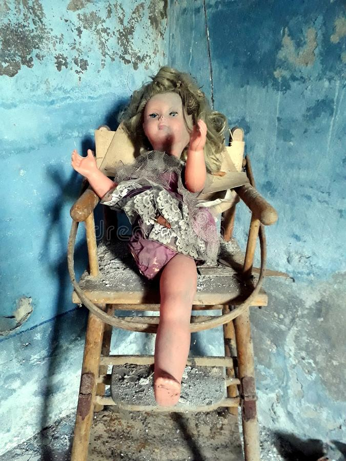 Horror doll on a chair. Brancere, Cremona, Italy. Horror doll without a leg sitting on a wooden chair. Elegant dress and beautiful face, toy of quality. Creepy royalty free stock photo