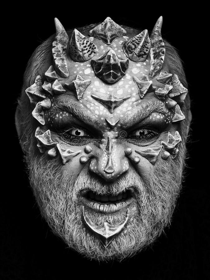 Horror and fantasy concept. Alien or reptilian makeup with sharp thorns and warts. Man with dragon skin and beard. Demon head isolated on black. Monster face royalty free stock photo