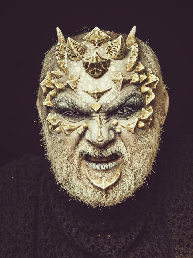 Horror and fantasy concept. Demon head on black background. Man with dragon skin and beard. Alien or reptilian makeup with sharp thorns and warts. Monster face royalty free stock photography