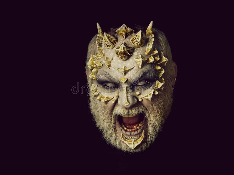 Horror and fantasy concept. Demon baring teeth isolated on black. Man angry with blind eyes. Evil face with dragon skin and grey beard. Monster with thorns and stock photo