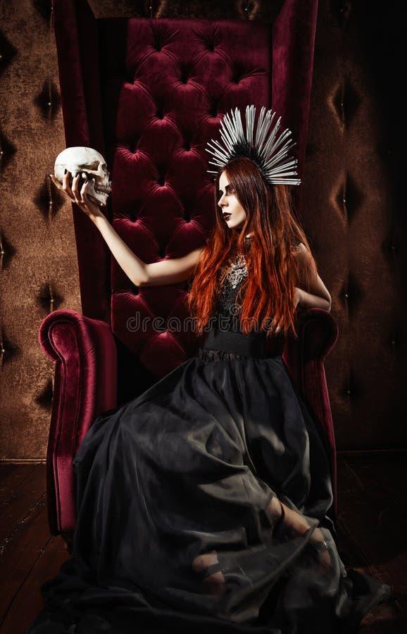 Horror fotografia: piękna goth dziewczyna w czerni sukni trzyma czaszkę fotografia royalty free
