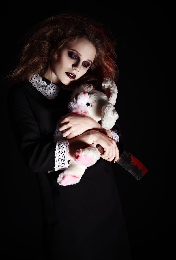 Horror geschossen: trauriges gotisches Mädchen mit Kaninchenspielzeug und blutigem Messer in den Händen lizenzfreies stockfoto