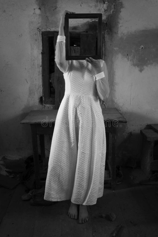 Horror girl in creepy old interior holding mirror. Horror ghost girl in creepy old interior holding a mirror royalty free stock photography