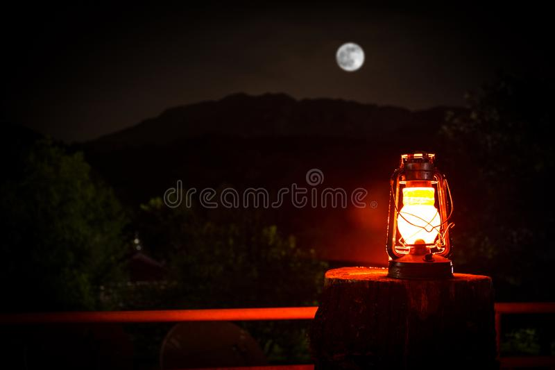 Horror Halloween concept. Burning old oil lamp in forest at night. Night scenery of a nightmare scene. royalty free stock photography