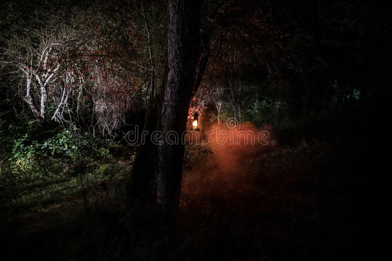 Horror Halloween concept. Burning old oil lamp in forest at night. Night scenery of a nightmare scene. Selective focus stock images