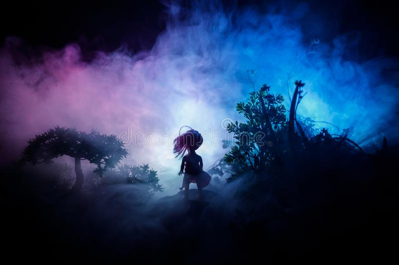 Horror Halloween decorated conceptual image. Alone girl with the light in the forest at night. Silhouette of girl standing between. Trees with surreal light on royalty free stock photos