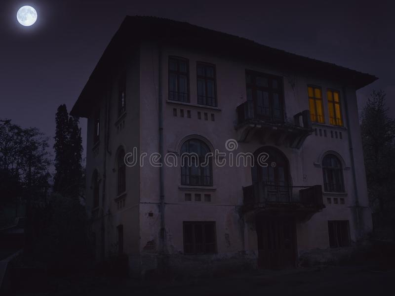 Horror house in  dark dramatic atmosphere. With full moon and light inside stock photo