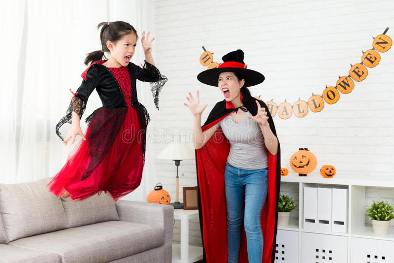 Horror little witch girl jump from the sofa stock photo