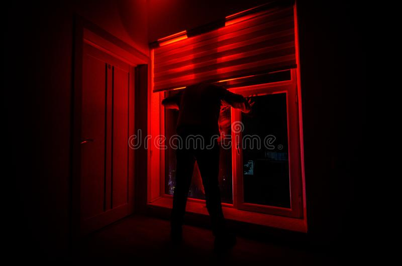 Horror man in window scary scene halloween concept Blurred silhouette of ghost. Horror theme stock photos